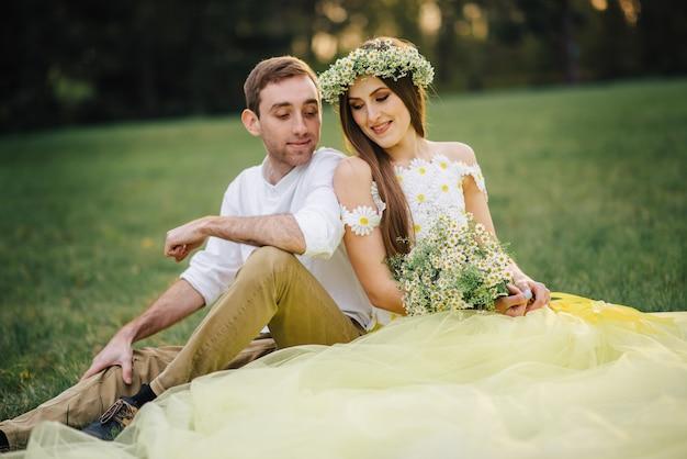 Giovani sposi felici che si siedono sull'erba nel parco al tramonto