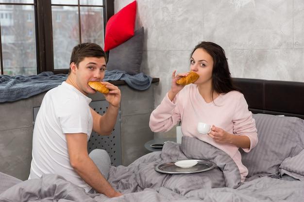 La giovane coppia felice si è appena svegliata, mangiando croissant e facendo colazione a letto, in pigiama, nella camera da letto in stile loft