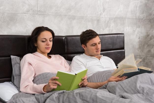 Giovane coppia felice che legge libri mentre è sdraiata a letto e indossa un pigiama in camera da letto in stile loft con colori grigi