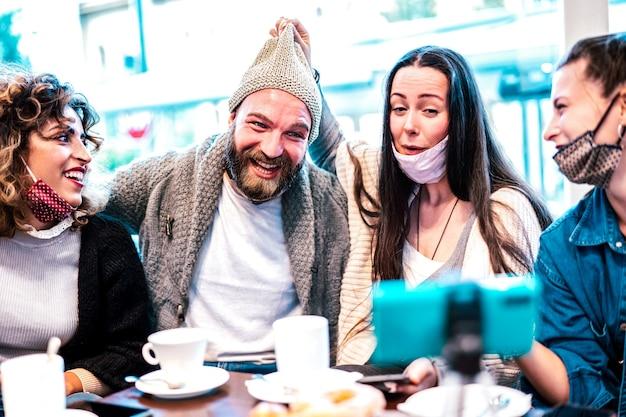 Giovani felici che condividono contenuti sulla piattaforma di streaming indossando una maschera facciale aperta