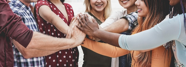 Giovani felici che impilano le mani all'aperto