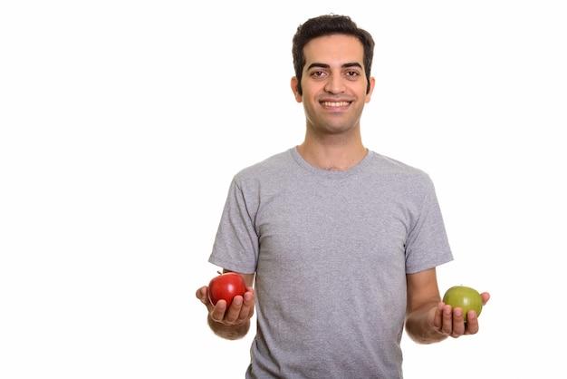 Giovane uomo persiano felice che tiene mela rossa e verde pronta per la palestra