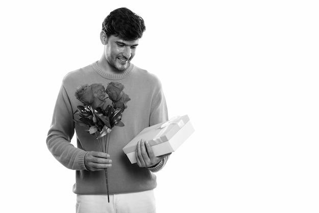Giovane uomo persiano felice che sorride mentre tiene e che esamina le rose rosse e la confezione regalo pronta per il giorno di san valentino