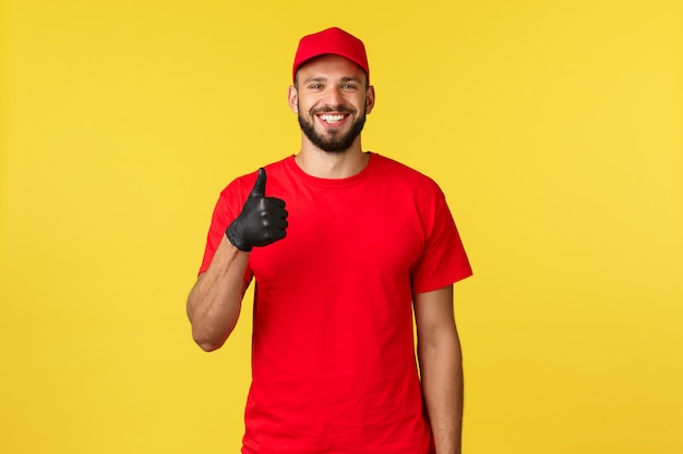 Giovane felice, compiaciuto corriere con la barba in uniforme e berretto da compagnia, indossa guanti protettivi, mostra pollice in su e sorride