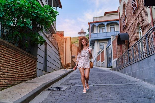 Giovane felice sorridente bella ragazza bruna viaggiatrice carina con le gambe lunghe che indossa cappello, borsa di paglia rotonda e tuta corta che cammina da sola per la città al giorno di estate pieno di sole