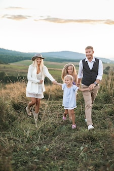 Giovane famiglia sorridente felice con due figlie divertirsi in campagna