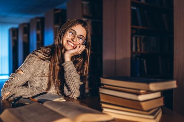 Giovane studente sorridente felice in bicchieri preparando per l'esame. ragazza di sera si siede a un tavolo in biblioteca con una pila di libri, sorridendo e guardando la telecamera