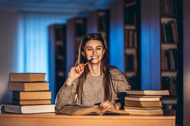 Giovane studente sorridente felice in bicchieri preparando per l'esame. ragazza di sera si siede a un tavolo in biblioteca con una pila di libri, sorridendo e guardando