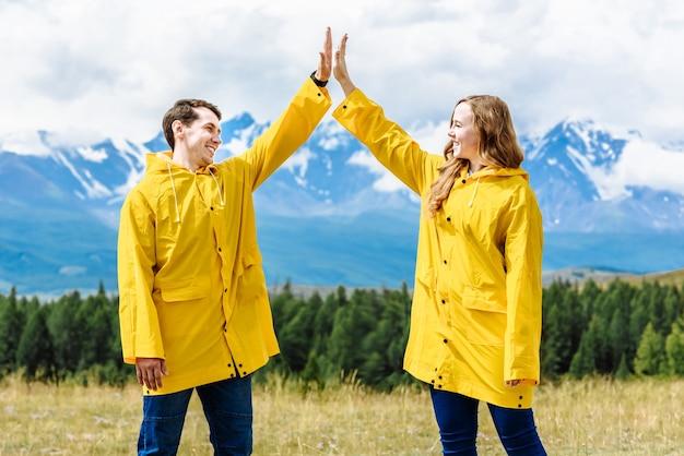 Giovani turisti felici e sorridenti uomo e donna in giacche impermeabili gialle
