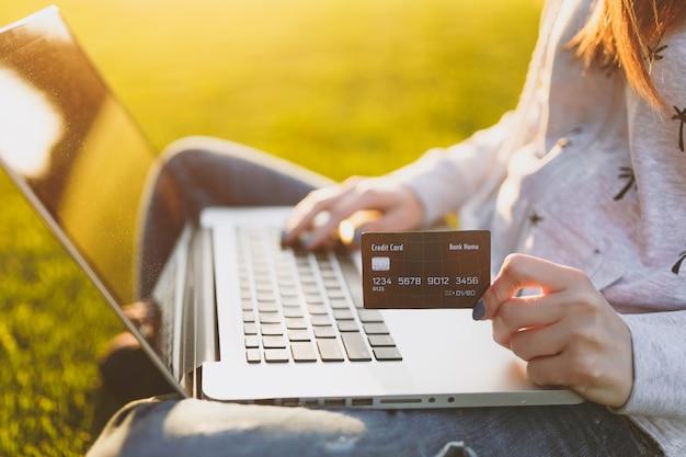 Giovane studentessa felice con carta di credito. donna seduta sul terreno di erba, lavorando su computer pc portatile nel parco cittadino sul prato verde del sole dell'erba all'aperto. ufficio mobile. concetto di business freelance.