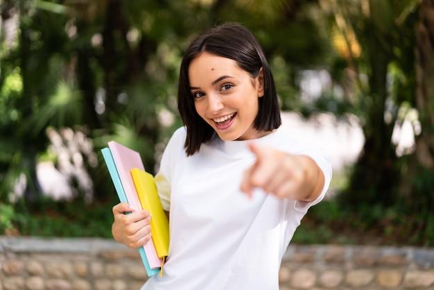 Giovane donna felice dell'allievo che indica la parte anteriore e che tiene i taccuini all'aperto