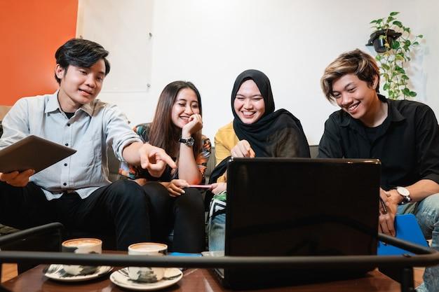 Giovani e adolescenti felici che vanno in giro e studiano insieme in un caffè
