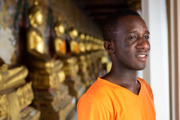 Giovane uomo turistico felice che sorride mentre pensando contro la vista delle strutture allineate di buddha in tempio di wat arun a bangkok tailandia
