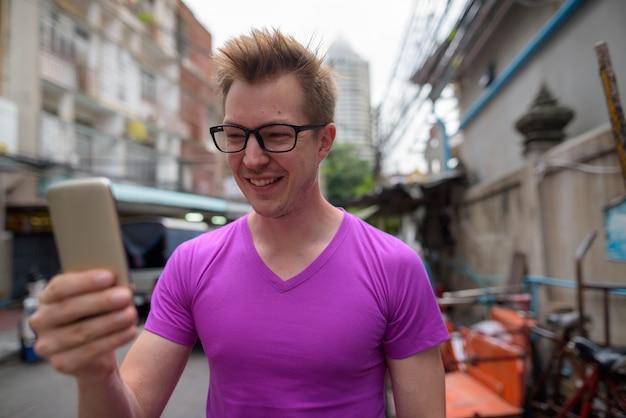 Felice giovane turista uomo utilizzando il telefono cellulare a bangkok