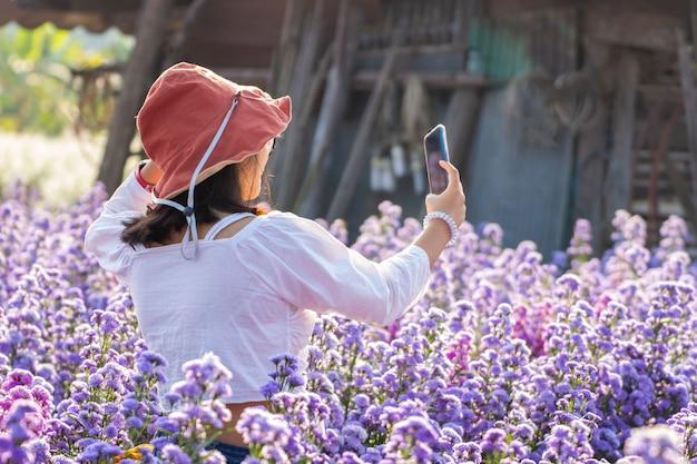 Giovane donna asiatica felice del viaggiatore con il vestito e la corona di fiori facendo uso del telefono astuto che si rilassa