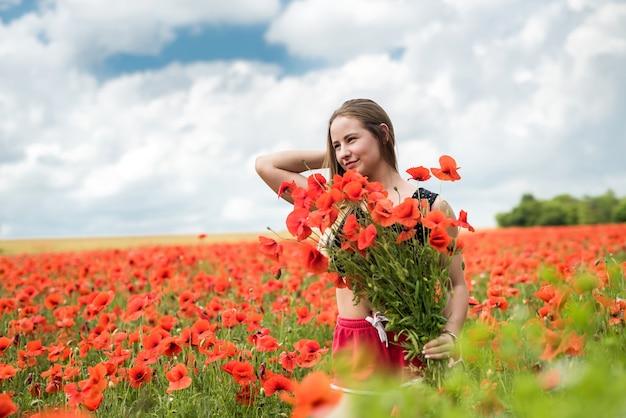 La giovane donna ucraina felice che tiene il mazzo dei fiori del papavero cammina e gode della giornata di sole nel campo