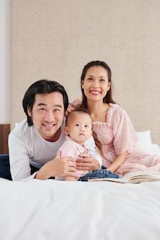 Giovane marito e moglie vietnamiti felici che abbracciano il piccolo figlio quando si guarda un cartone animato o un film sul televisore