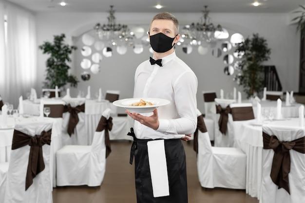 Giovane cameriere felice che indossa una maschera protettiva mentre serve cibo in un ristorante.