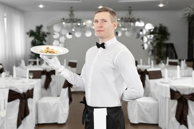 Giovane cameriere felice mentre serve cibo in un ristorante.