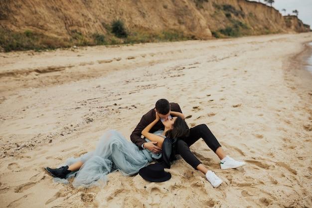 Giovani sposi felici che si rilassano insieme sulla spiaggia tropicale al mare azzurro.