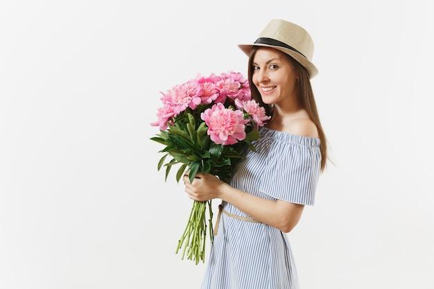 Giovane donna felice in abito blu, cappello con bouquet di bellissimi fiori di peonie rosa isolati su sfondo bianco. san valentino, concetto di vacanza per la giornata internazionale della donna. zona pubblicità.