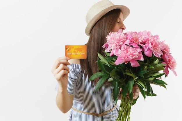 Giovane donna felice in abito blu, cappello in possesso di carta di credito, denaro, bouquet di bellissimi fiori di peonie rosa isolati su sfondo bianco. affari, consegna, concetto di shopping online. copia spazio.
