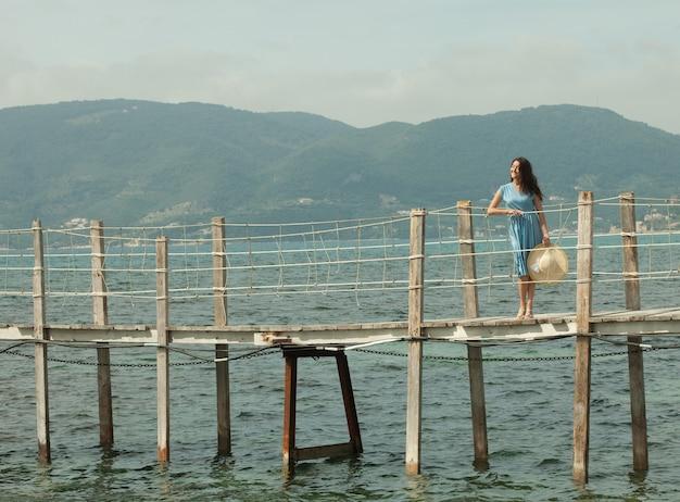 Giovane donna felice sul ponte vicino al mare, periodo estivo