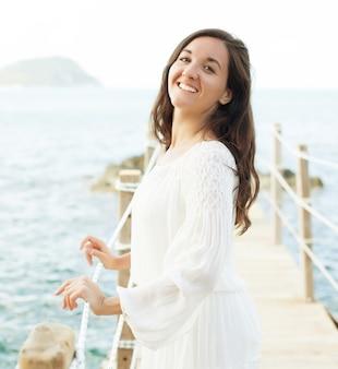Giovane donna felice sul ponte vicino al mare, ora legale