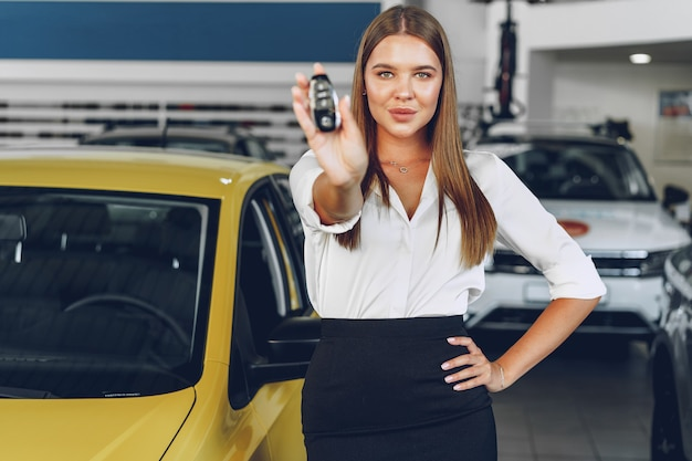 Giovane donna felice acquirente / venditore vicino all'auto con le chiavi in mano si chiuda