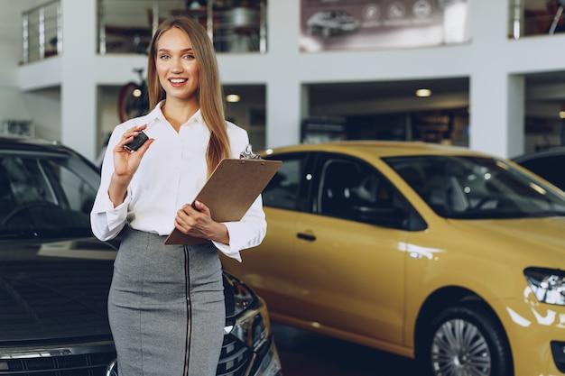 Venditore di auto giovane donna felice vicino alla macchina con le chiavi in mano
