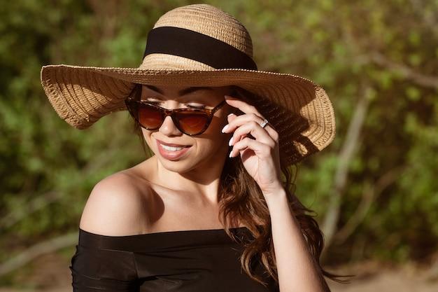 Giovane donna felice di aspetto caucasico in un primo piano del cappello di paglia in occhiali da sole in posa su una soleggiata giornata estiva sulla spiaggia