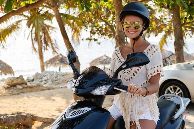 Giovane donna felice alla guida di scooter sulla spiaggia tropicale