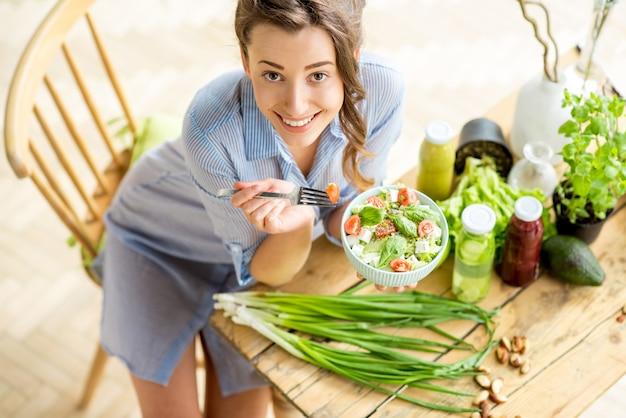 Giovane e donna felice che mangia insalata sana seduta sul tavolo con ingredienti freschi verdi al chiuso