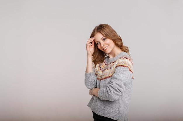 Giovane donna felice in un maglione vintage di moda su uno sfondo grigio