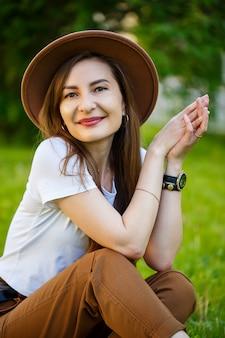 La giovane donna felice in un cappello si siede su un prato verde in un parco. una ragazza di aspetto europeo con un sorriso sul viso in una luminosa giornata estiva di sole