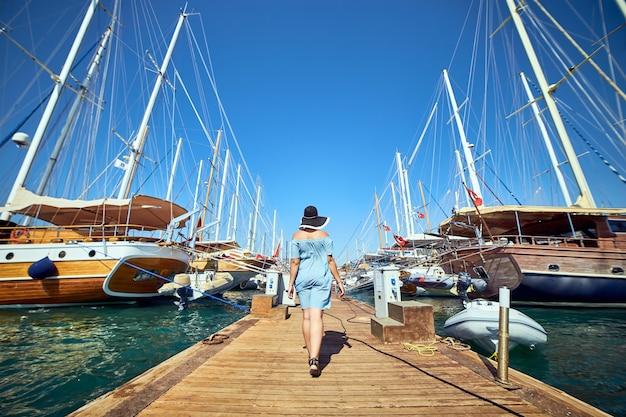 Giovane donna felice in cappello in piedi vicino al porto marittimo con yacht di lusso