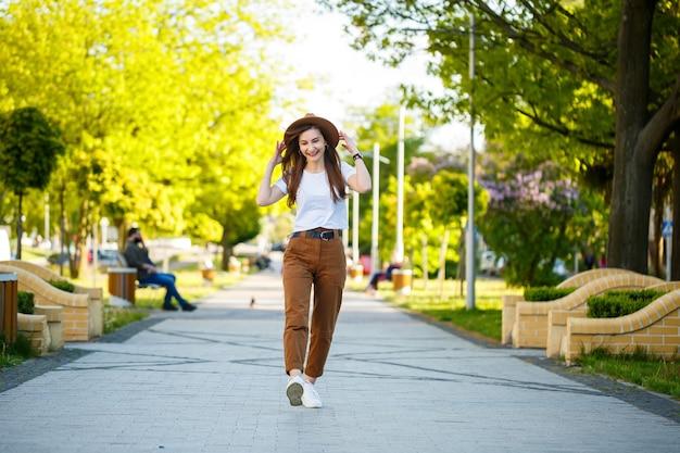 La giovane donna felice in un cappello cammina lungo un vicolo in un parco. una ragazza di aspetto europeo con un sorriso sul viso in una luminosa giornata estiva di sole