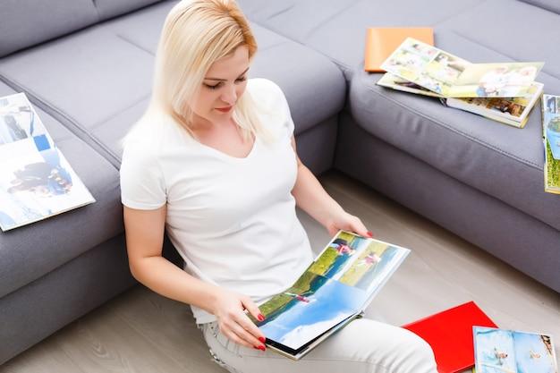 Giovane donna felice che guarda il fotolibro nella sua stanza