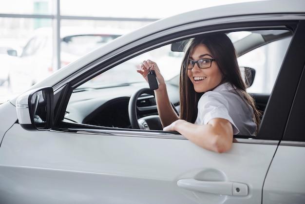 Giovane donna felice vicino all'automobile con le chiavi in mano