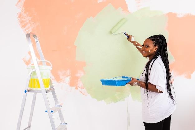 Giovane donna felice pittura parete interna con rullo di vernice nella nuova casa