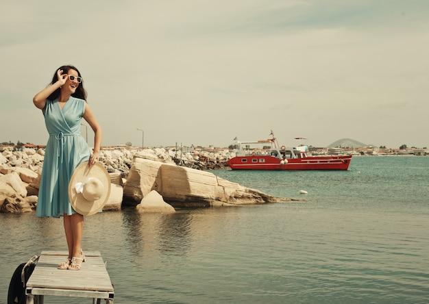 Giovane donna felice che propone vicino al mare, vacanze estive