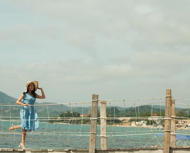 Giovane donna felice in posa vicino al mare, vacanze estive