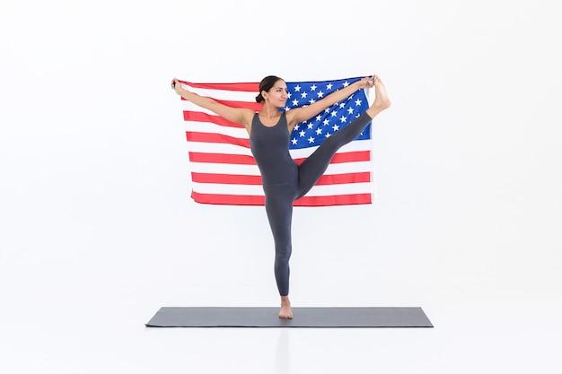 Giovane donna felice che pratica yoga sul tappetino non sfondo bianco