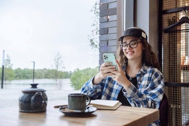 La giovane donna felice si siede in un caffè e usa il telefono per comunicare nel messenger