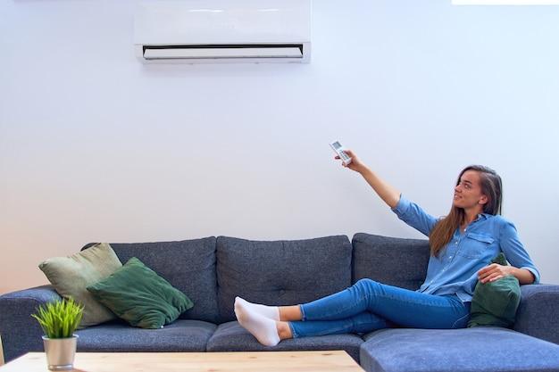 Giovane donna felice che si siede sul divano sotto il condizionatore d'aria e regolazione della temperatura comfort con telecomando a casa moderna
