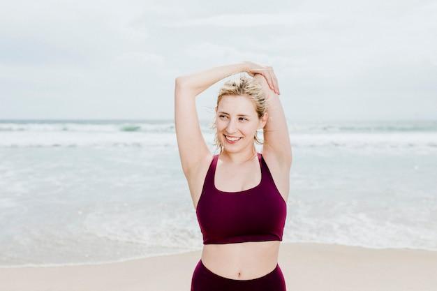 Giovane donna felice che si estende sulla spiaggia?
