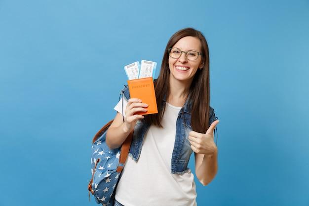 Giovane studentessa felice in bicchieri con zaino in possesso di passaporto, biglietti per la carta d'imbarco e mostrando pollice in su isolato su sfondo blu. istruzione in college universitario all'estero. volo aereo.