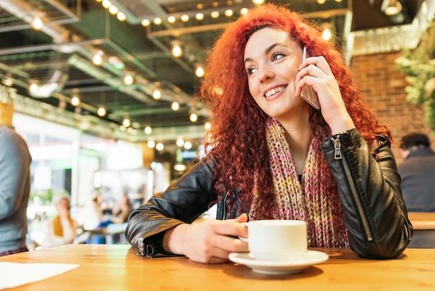 Giovane donna felice che parla al telefono nella caffetteria.