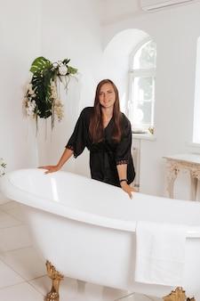 Giovane donna felice che indossa accappatoio in bagno con pareti in marmo. concetto di relax mattutino.