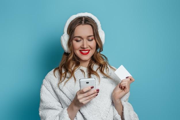 La giovane donna felice in cappotto di pelliccia sintetica bianca invernale e cuffie in pelliccia tiene il telefono cellulare e la carta di credito e fa l'ordine online, lo shopping